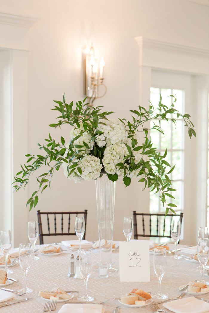 Tall Centerpieces with white wedding flowers and greenery at Raleigh wedding venue Highgrove Estate