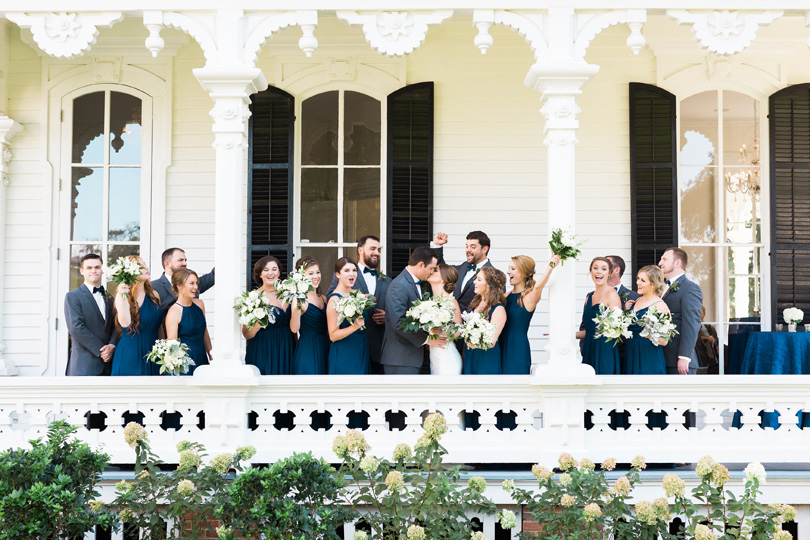 Bridal Party in navy and grey with white floral bouquets on porch at The Merrimon Wynne by Gather Together, Melissa Delorme