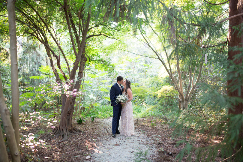 Bride and Groom embrace in Duke Gardens in BHLDN dress and Navy Menguin suit with golden sun Duke Gardens wedding by Gather Together Photography by Katherine Miles Jones (1)