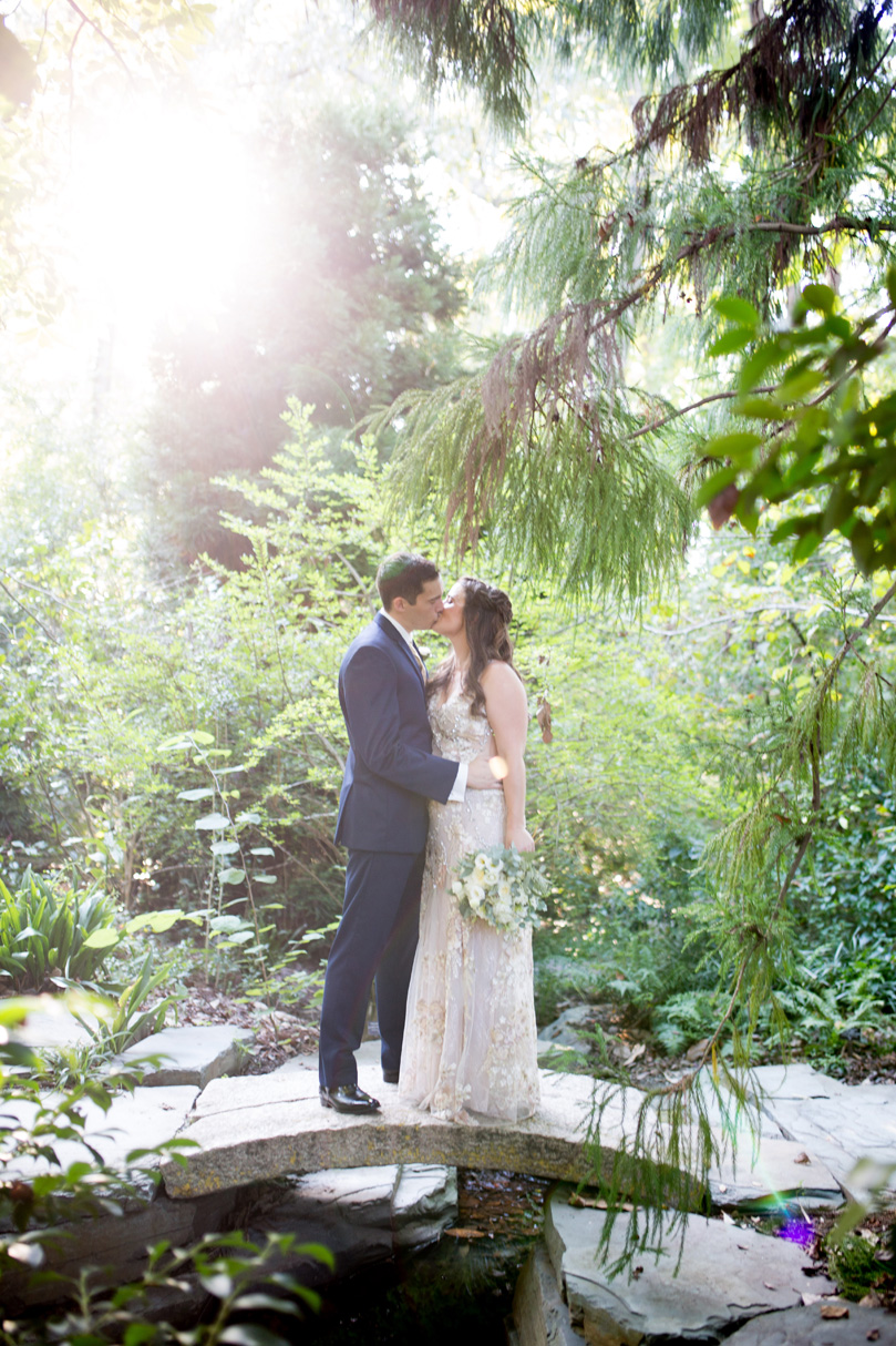 Bride and Groom embrace in Duke Gardens in BHLDN dress and Navy Menguin suit with golden sun Duke Gardens wedding by Gather Together Photography by Katherine Miles Jones