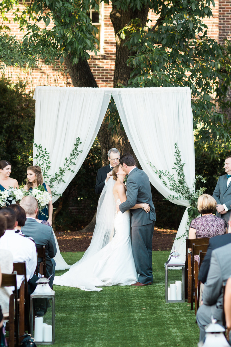 Bride and Grooms first kiss under white drapery at The Merrimon Wynne by Gather Together, Melissa Delorme