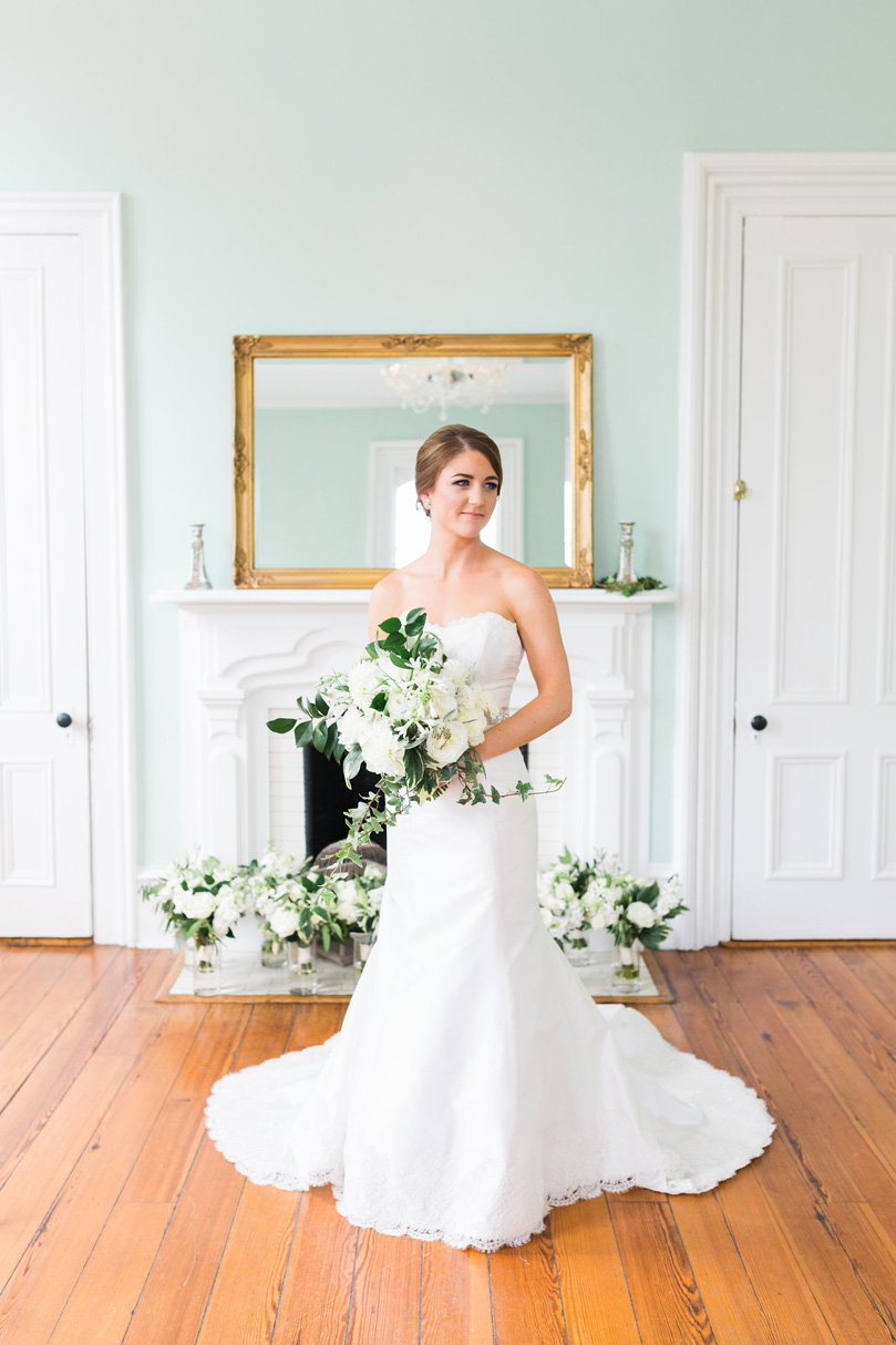 Bride in Lea Ann Strapless Gown holding large white and leaf bridal bouquet at The Merrimon Wynne by Gather Together, Melissa Delorme