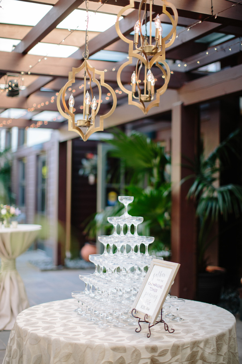 Champagne Glasses Stacked at NC Duke Gardens Wedding with Gold Accent Light hangings by Get Lit Duke Gardens Reception by Gather Together photographed by Katherine Miles Jones.