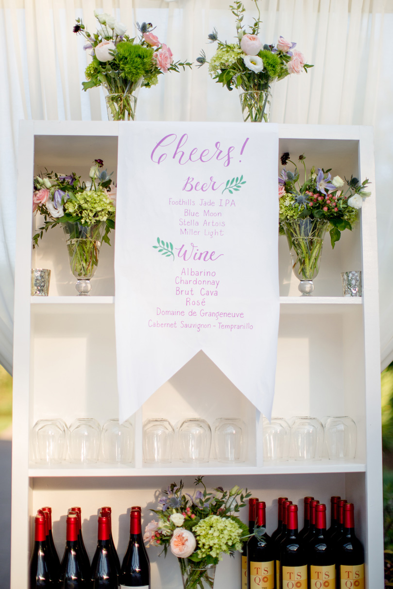 Cheers bar menu sign hanging above wine bottles at NC Duke Gardens wedding Duke Gardens Reception by Gather Together photographed by Katherine Miles Jones