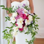 Bride in Lana Addison Bridal Dress holding large spring bouquet with white purple and pink blooms and large vines by Bloom Works, Katherine Miles Jones Photography