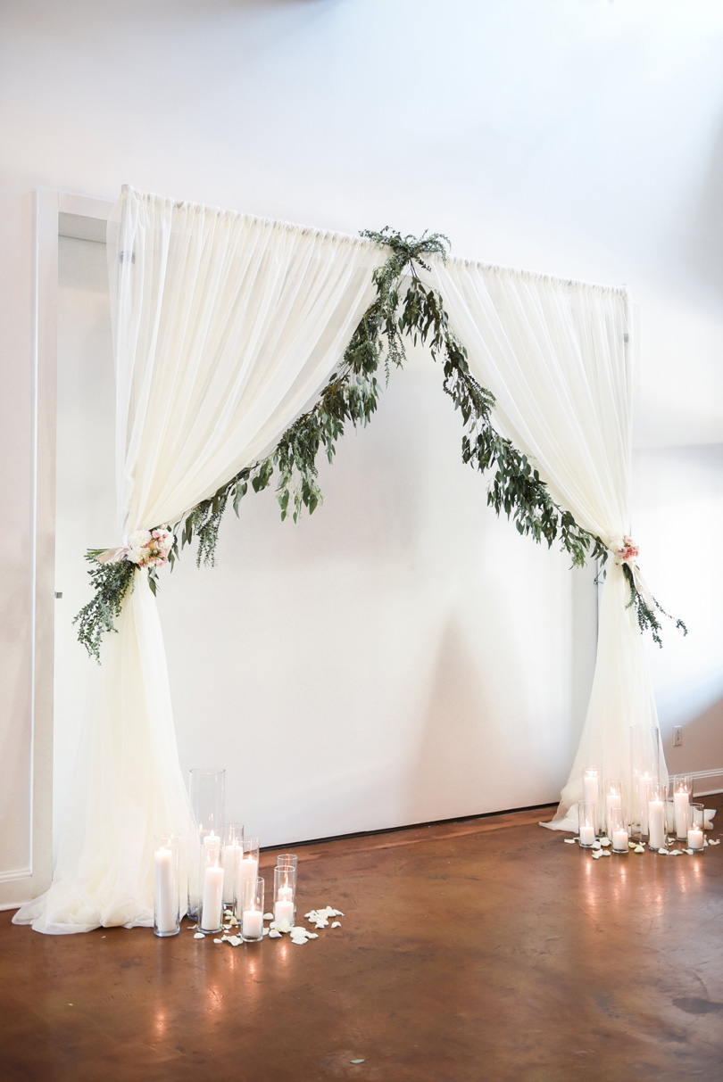 Linen and greenery arbor with floor candle decor for wedding at Market Hall Raleigh NC Missy Loves Jerry Photography