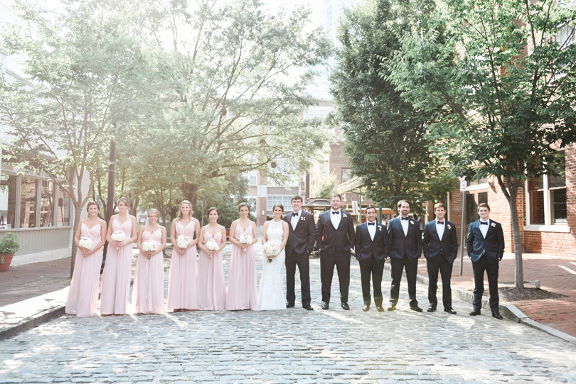 Wedding party in blush and groomsmen in navy in market hall raleigh wedding Missy Loves Jerry Photography
