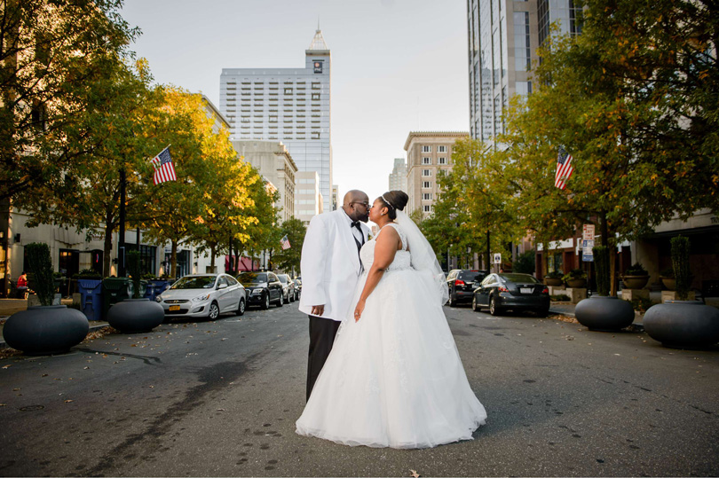 Bride and Groom kiss downtown raleigh at Raleigh Marriott City Center In His Image