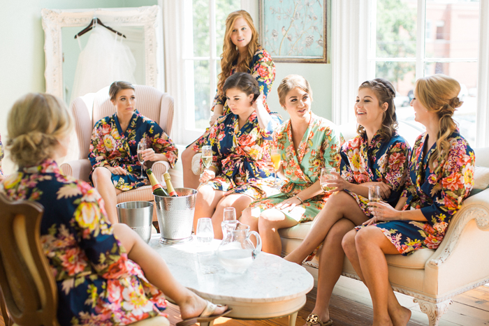 Bridesmaids-in-floral-robes-getting-ready-for-wedding-in-bridal-suite-at-The-Merrimon-Wynne-by-Gather-Together,-Melissa-Delorme