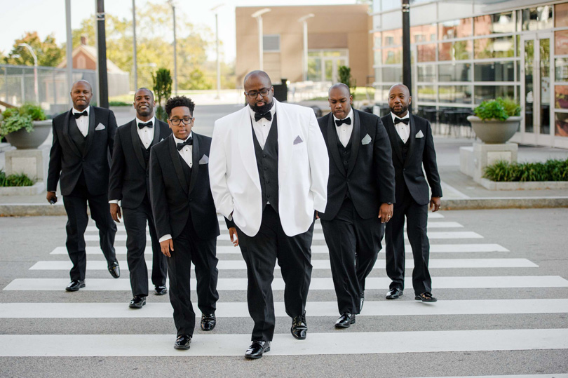 Grooms party in black tuxedos walking in downtown raleigh Black classic tux with striped hankerchief at Raleigh wedding In His Image