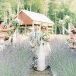 Bride and Groom Walking through Lavender Oaks Farm Fields of Purple Chapel Hill NC Wedding Venue Barn Adelyn Boling