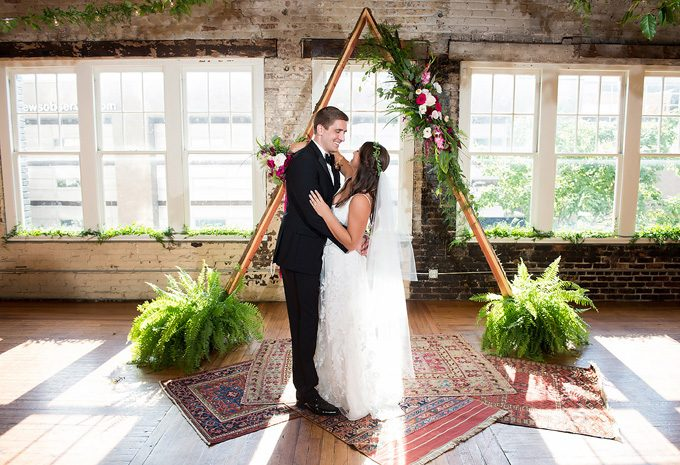Bride in kate mcdonald gown from gilded and groom in front of a frame wedding arbor at The stockroom in raleigh, brian mullins
