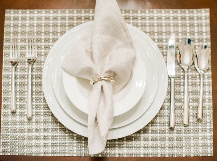 Crate and Barrel white china with vinyl placemat and elgant silver napkin ring and silverware by Fancy This Photography