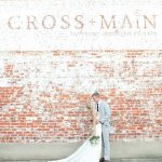 Couple outside of Cross and Main Sign on brick wall