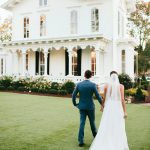bride and groom walking outside of the Merrimon Wynne House downtown Raleigh wedding venue