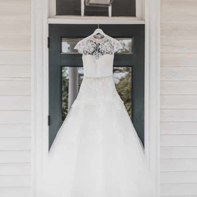 Vintage Style White Bridal Gown with Lace Neckline and Tulle Hanging on Venue Door at The Sutherland