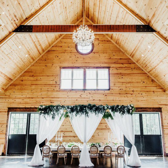 Drapery and Greenery on Head Table Under Crystal Chandelier Wedding Reception The Carolina Barn Rustic Farm NC Wedding Venue Caddell